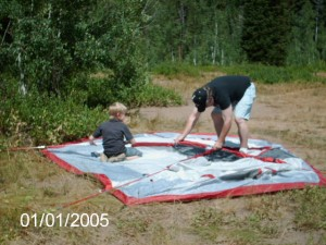 His dad showing him how to set up the tent.
